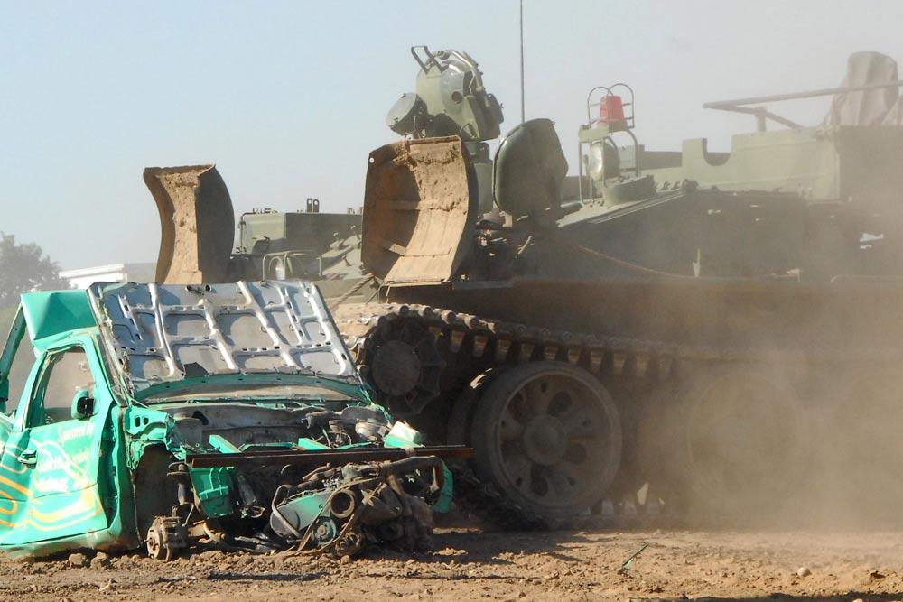 Die brachiale Gewalt von 34 Tonnen Stahl des T 55 Bergepanzers rollt auf einen ausgeschlachteten Pkw zu